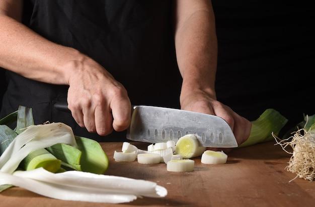Gros plan d'un cuisinier coupant un poireau sur bois