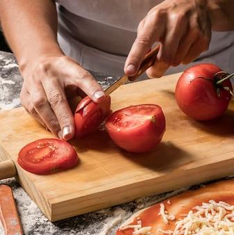 Gros plan, cuisinier, découpage, tomate