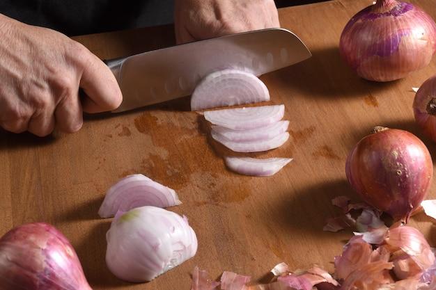 Gros plan d'un cuisinier éplucher un oignon sur un bois