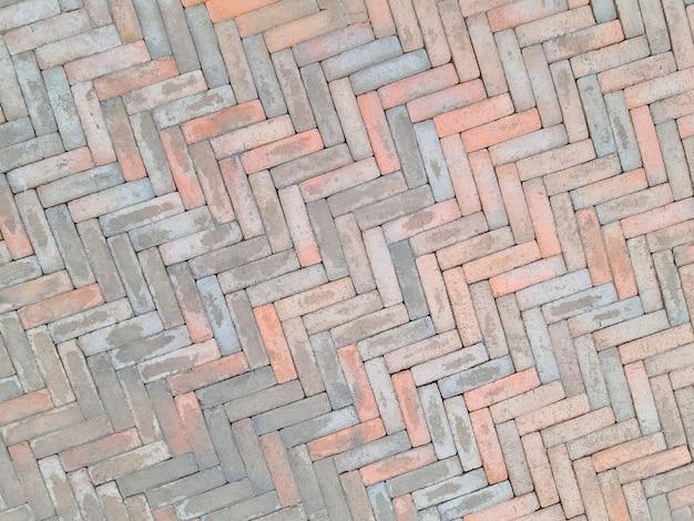 Gros plan des dalles de pavage rose et gris sur fond de rue de la ville