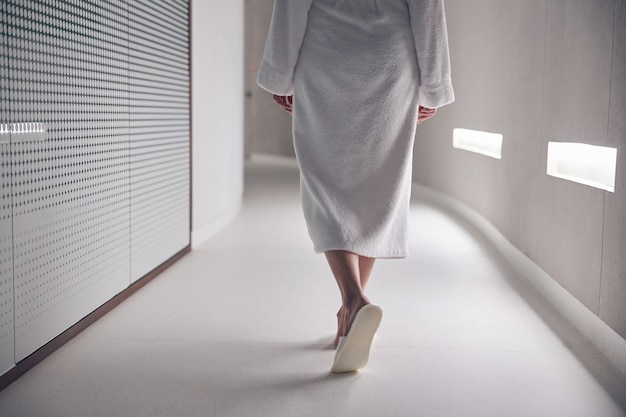 Gros plan sur une dame en chaussons marchant le long du couloir dans un salon spa