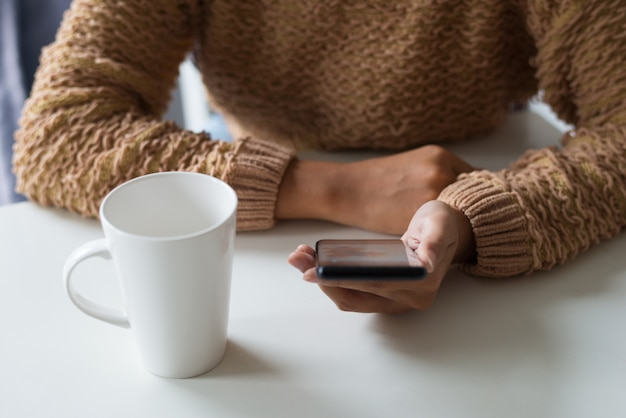 Gros plan, de, dame, dans, pull chaud, utilisation, smartphone, dans, bureau