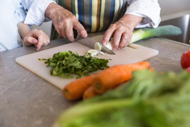 Gros plan d'une dame senior, couper les légumes sur une planche