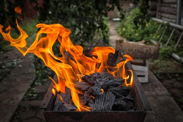 Un gros plan dans un grill métallique brûle un feu de braises pour faire frire le shish kebab en arrière-plan