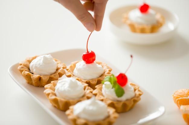 Gros plan de la décoration à la main de mini tartes à la crème avec de la cerise