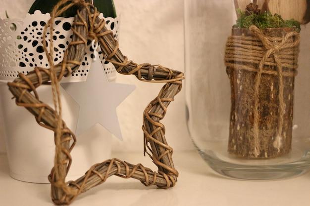 Gros plan de décors rustiques d'étoile en osier et bois avec ficelle de jute dans un verre