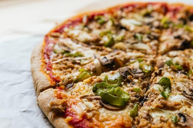 Gros plan d'une délicieuse pizza italienne maison avec fromage, tomates, champignons et poivron vert