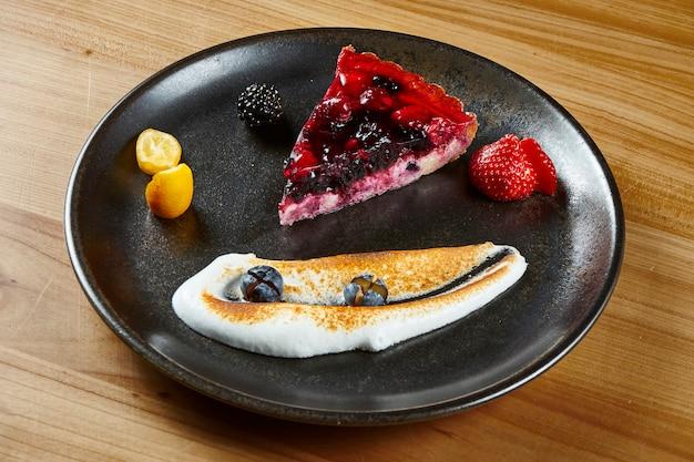 Gros plan sur une délicieuse tranche de gâteau au fromage aux baies aérées délicates sur une plaque sombre