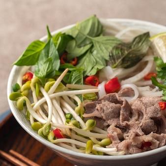 Gros plan de délicieuses nouilles de bœuf vietnamiennes pho dans un bol avec des ingrédients avec espace de copie.