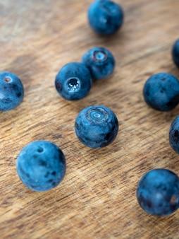 Gros plan de délicieux bleuets mûrs sur un fond en bois. produits naturels sains, vitamines. mise au point sélective. vue de dessus, mise à plat.
