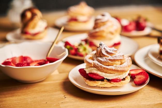 Gros plan de délicieux choux à la crème aux fraises sur une table en bois