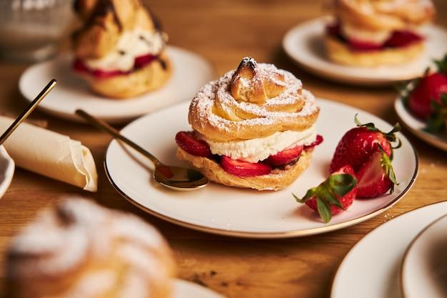 Gros plan de délicieux choux à la crème avec des fraises sur une table en bois