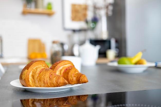 Gros plan de délicieux croissants se trouvent sur une assiette sur la table de la cuisine mise au point sélective floue