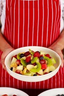 Gros plan de délicieux délicieux délicieux apéritif de salade de fruits mélangés sucrés pomme kiwi myrtille raisin dans un bol blanc sur les mains d'une femme chef exécutive qui se tient debout porte un tablier rouge à rayures derrière en arrière-plan.