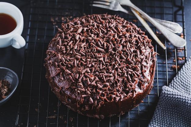 Gros plan d'un délicieux gâteau au chocolat avec des morceaux de chocolat sur une plaque à pâtisserie.