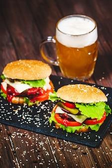Gros plan de délicieux hamburgers faits maison avec un couteau collé sur un plateau en pierre. sombre