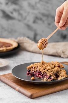 Gros plan délicieux morceau de tarte à la main avec du miel
