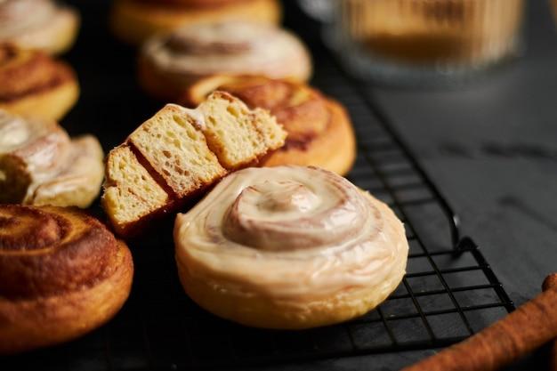 Gros plan de délicieux petits pains à la cannelle avec glaçage blanc sur un tableau noir