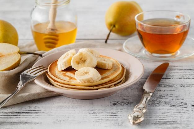 Gros plan délicieux et sain petit déjeuner de crêpes au miel, noix et bananes caramélisées sur une surface en bois avec copie espace