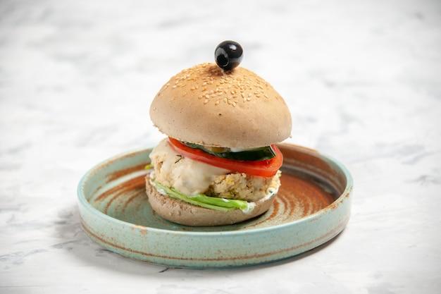 Gros plan d'un délicieux sandwich fait maison à l'olive noire sur une assiette sur une surface blanche tachée avec espace libre
