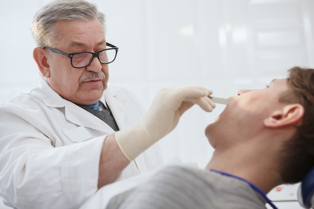 Gros plan d'un dentiste senior masculin examinant les dents d'un patient