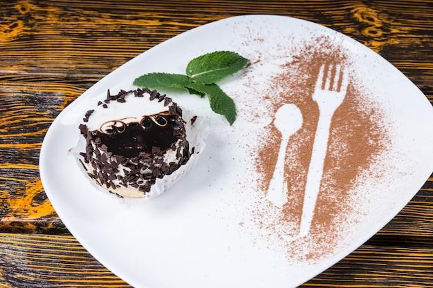 Gros plan sur un dessert décadent enrobé de copeaux de chocolat et servi sur une assiette avec une garniture de feuilles de menthe et des contours d'ustensiles saupoudrés de cacao et reposant sur une surface de table en bois