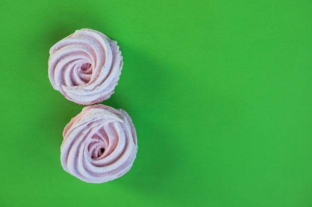 Gros plan dessert fraîchement cuit au four meringues zèphyr guimauve gâteau isolé sur mur vert. dessert aux bonbons.