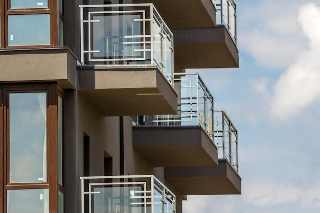 Gros plan, détail, de, mur, immeuble, à, balcon, et, fenêtres brillantes, sur, ciel bleu.