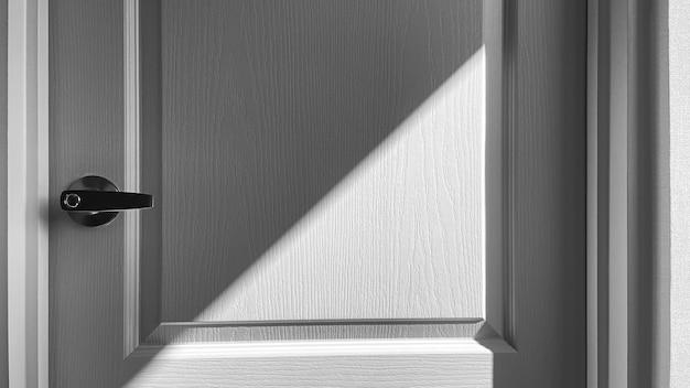 Gros plan détail de porte blanche avec ombre, fond noir et blanc.