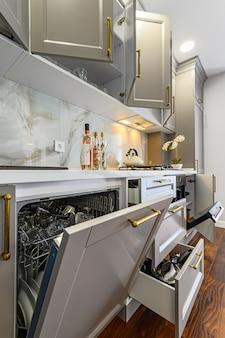 Gros plan des détails de la cuisine classique contemporaine gris et blanc conçu dans un style moderne, toutes les portes et tiroirs de meubles sont ouverts