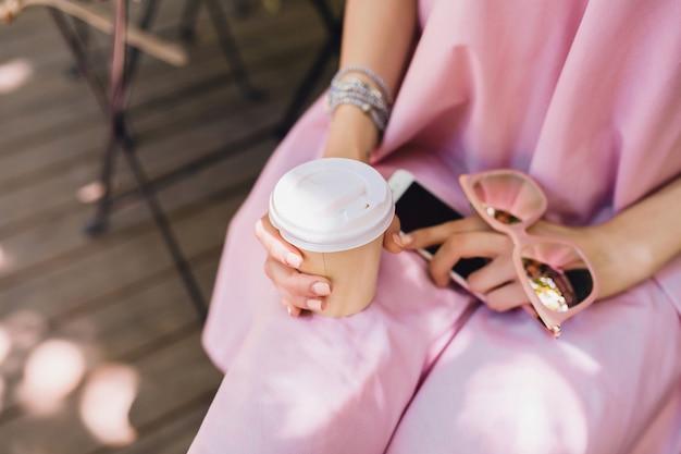 Gros plan sur les détails des mains d'une femme assise dans un café en tenue de mode estivale