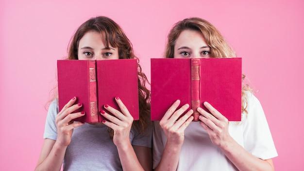 Gros plan de deux amies tenant un livre sous leurs yeux sur fond rose