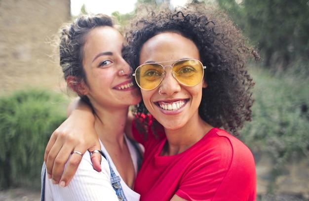 Gros plan de deux amis souriant tout en prenant des photos à l'extérieur