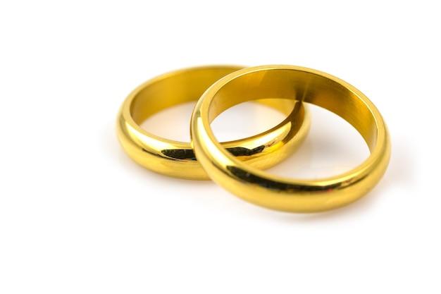 Gros plan de deux anneaux d'or pour mariage isolé sur fond blanc