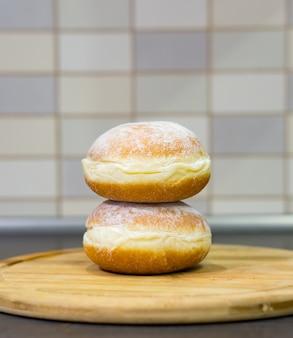 Gros plan de deux beignets de sucre frais sur une planche de bois