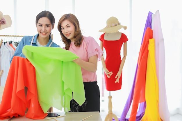Gros plan de deux belles créatrices de mode asiatiques heureuses choisissant un tissu à partir de divers tissus pour coudre leur nouvelle collection ensemble.
