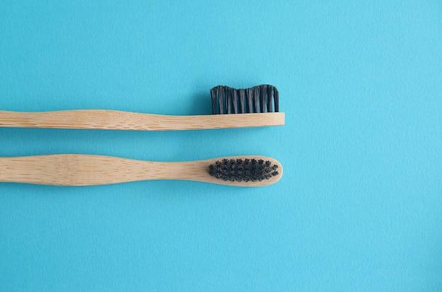 Gros plan de deux brosses à dents en bambou sur fond bleu
