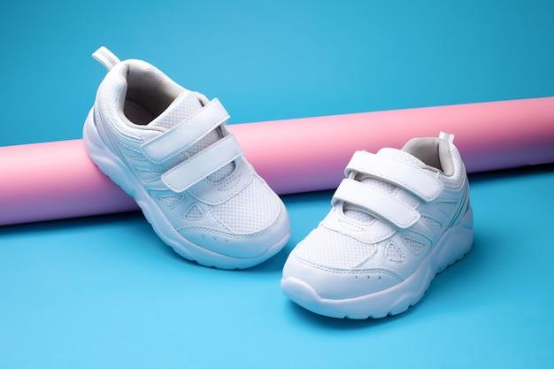 Gros plan sur deux chaussures de sport femme blanche sur un long tube de papier rose sur fond bleu géométrique dans un t...