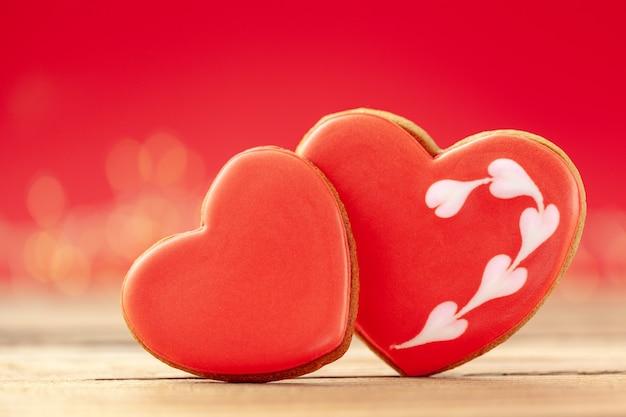 Gros plan deux coeurs rouges en pain d'épice pour la saint valentin, la fête des mères ou un anniversaire sur fond rouge.