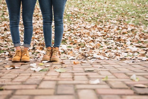 Gros plan de deux femmes en bottes debout dans le parc