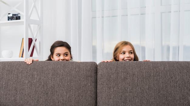 Gros plan, deux, filles, cacher, derrière, les, gris, sofa, regarder appareil-photo
