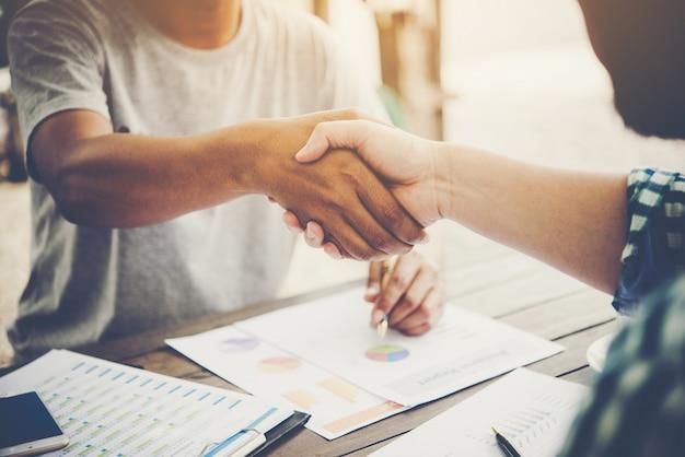 Gros plan de deux hommes d'affaires serrant la main pendant que vous vous asseyez sur le lieu de travail.