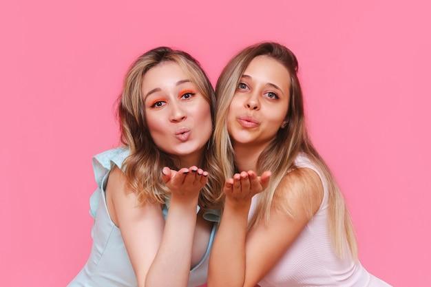 Gros plan de deux jeunes belles femmes élégantes caucasiennes dans des robes élégantes envoient un baiser aérien avec les paumes ouvertes regardant à l'avant isolées sur un mur rose de couleur claire
