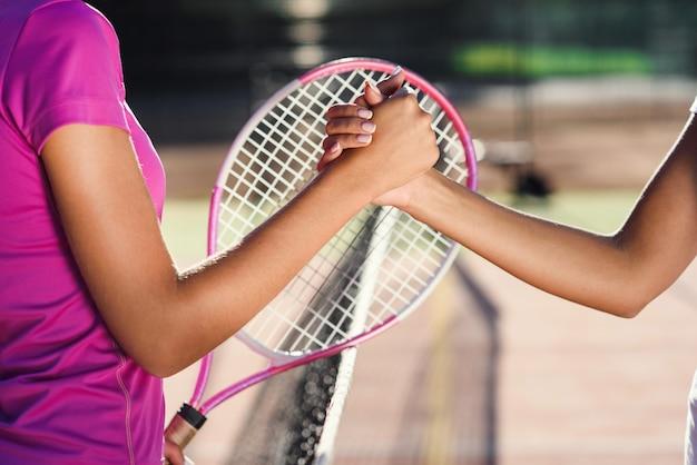 Gros plan sur deux jeunes joueuses de tennis se serrant la main sur le net. poignée de main amicale après la fin du tournoi de tennis.