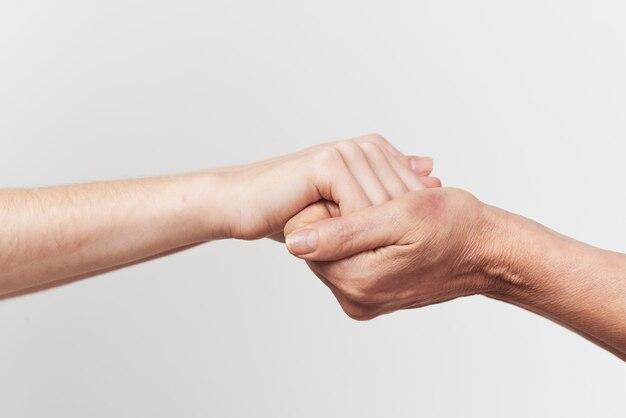 Gros plan de deux mains se tenant l'aide de la famille