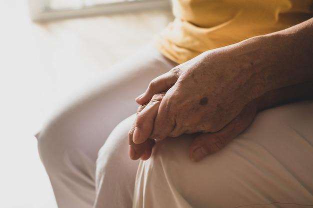 Gros plan de deux mains se tenant ensemble à la maison en prenant soin - mains de personnes âgées et matures