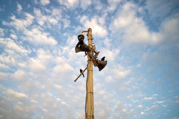 Gros plan de deux mégaphones extérieurs sur poteau avec deux oiseaux noirs contre le ciel bleu nuageux. deux vieux haut-parleurs poussiéreux sur le poteau. connexion et signal d'avertissement. amplifier la voix