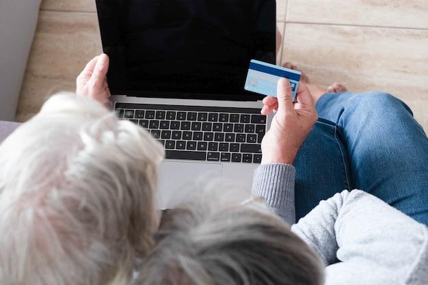 Gros plan sur deux personnes d'âge mûr utilisant une carte de crédit faisant des achats en ligne ensemble à la maison sur le canapé - les personnes âgées dépensent de l'argent