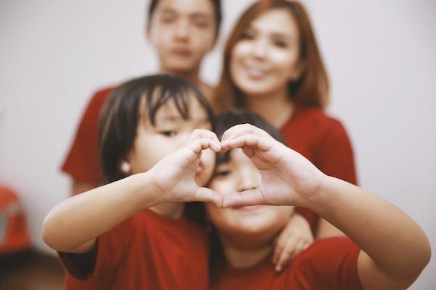 Gros plan de deux petites filles en forme de coeur avec les mains avec une photo floue du parent sur le fond concept d'amour et de famille heureuse