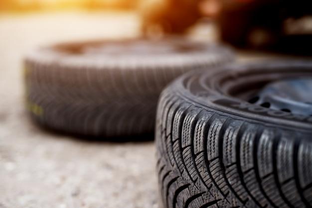 Gros plan de deux pneus neufs posés sur le trottoir l'un à côté de l'autre dans un atelier automobile.